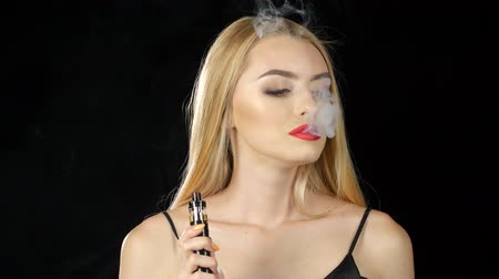 tabaco : Girl of extraordinary beauty smokes an electronic cigarette. Black background Stock Footage