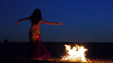 kudrnatý : Curly brunette dancing belly dance near the fire, in the background sunset