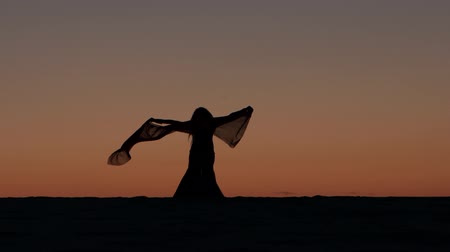 gracioso : Dancer dancing against the sunset dance the belly dance. Silhouette