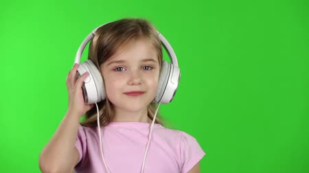 klucz : Baby listens to music through the headphones. Green screen. Slow motion