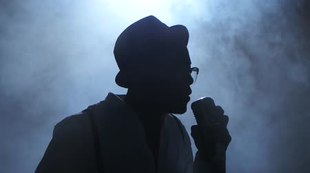 singers : Man young african american in half of the turnover in the smoke and white light approaching the microphone singing in a recording studio. Black background. Silhouette. Close up