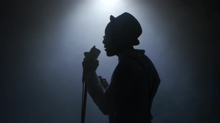 singers : Man african american in half of the turnover in the smoke and white light approaching the retro microphone singing in a recording studio. Black background. Silhouette. Close up