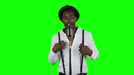 śpiew : Man singer sings into a microphone and dance. Green screen