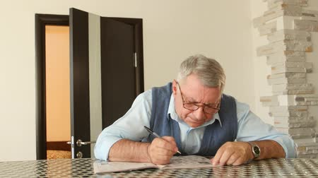 palavras cruzadas : Man unravels crossword puzzles, he has poor eyesight and he is wearing glasses Stock Footage