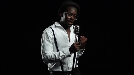 kayıt : Singer sings into a retro microphone spinning and dancing around him. Black background. Slow motion