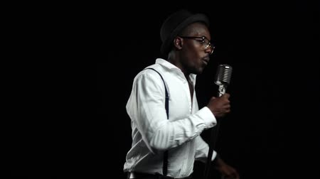 singers : Singer sings into a microphone spinning jumping and dancing around him. Black background. Slow motion. Close up