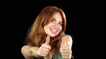 polegar : Girl showing thumbs up. Black background. Slow motion