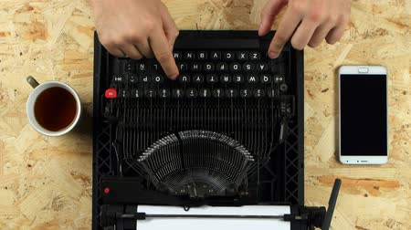 verse : Male hands typing on the typewriter. View from above