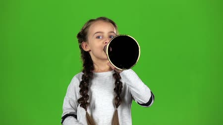 ouvido : Child speaks into the loudspeaker. Green screen. Slow motion