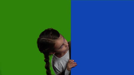 blank : Baby looks out from behind an empty board. Green screen. Slow motion