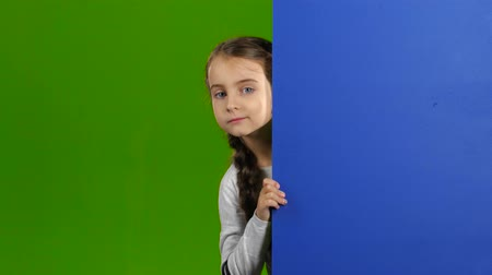 hides : Baby looks out from behind an empty board. Green screen