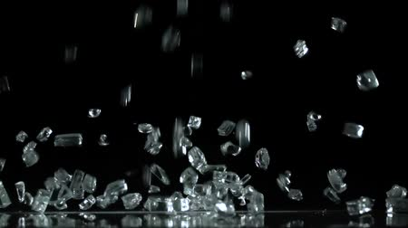 vítreo : Fragments of glass falling to the floor. Black background . Slow motion