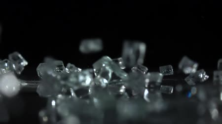 quebra : Crystals fall on a black background. Slow motion Stock Footage