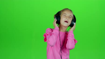 opus : Baby listens to the music in the headphones. Green screen Stock Footage