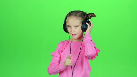 opus : Child listens to the music in the headphones. Green screen