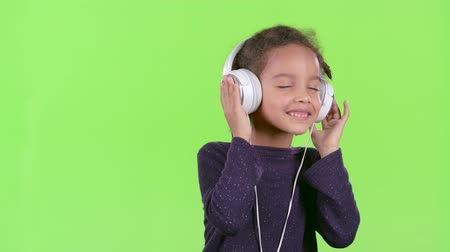 opus : Child of an african american listens to the music in the headphones. Green screen