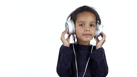 opus : Child of an african american listens to the music in the headphones. White background. Slow motion