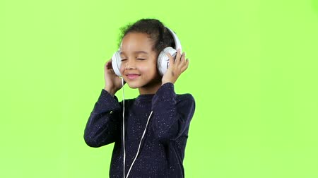opus : Child of an african american listens to the music in the headphones. Green screen. Slow motion Stock Footage