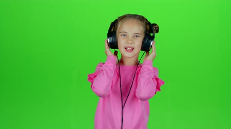 opus : Baby listens to the music in the headphones. Green screen. Slow motion