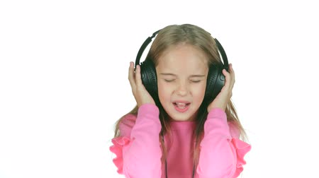 opus : Baby listens to the music in the headphones. White background. Slow motion