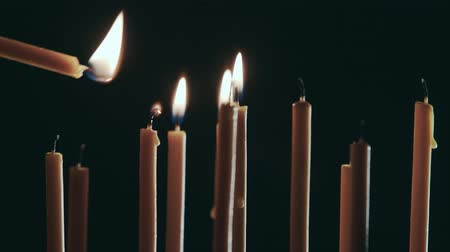cease fire : Person sets a candle in the temple. Black background Stock Footage