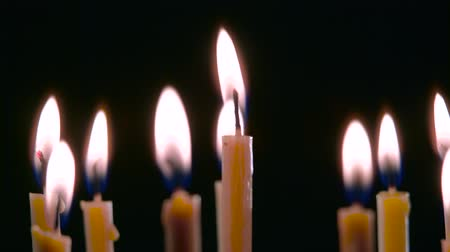 cease fire : Candles are burning in the spacious room and go out. Black background. Close up