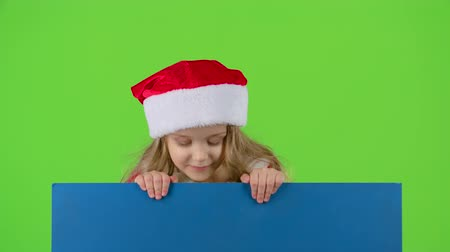 manó : Child girl in a New Years cap jumps and shows a finger down. Green screen. Slow motion Stock mozgókép