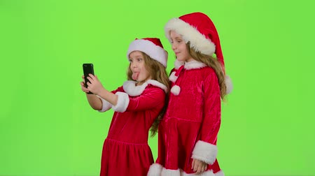 make photo : Two children in New Year costumes do selfie on the phone. Green screen