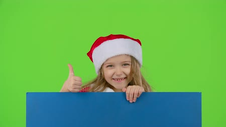 manó : Santa helper jumps out from behind the blue board and shows a thumbs up. Green screen