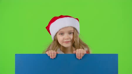 manó : Child in New Years clothes jumps out from behind the board and shows ok. Green screen