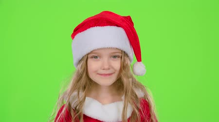 manó : Baby in a beautiful suit and a red New Years cap smiles. Green screen Stock mozgókép