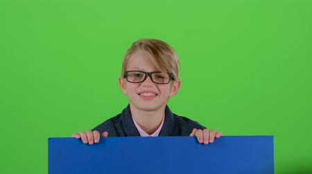 hides : Child boy in the glasses looks out from under the board holding on to her on a green screen