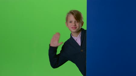 hides : Teenager peeks out from behind a board on a green screen Stock Footage