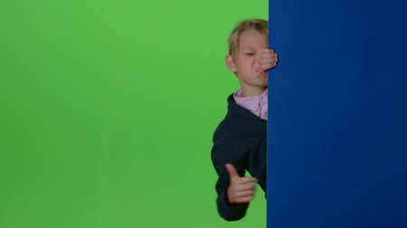 indicação : Teen peeks out from the side the boards and shows dislike on a green screen Stock Footage