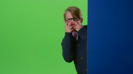 hides : Teen in glasses comes from behind the wall and shows tongue on a green screen Stock Footage