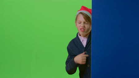 hides : Child boy in a christmas hat comes from behind the wall and shows tongue on a green screen