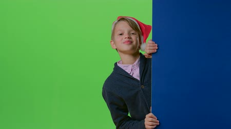 hides : Teen in christmas hat appears from the side boards on a green screen Stock Footage