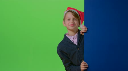 hides : Teen in christmas hat with bubon appears from the side boards on a green screen
