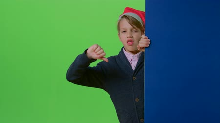hides : Child boy in a christmas hat appears from the side of the board holding her hands in front then shows dislike on a green screen Stock Footage