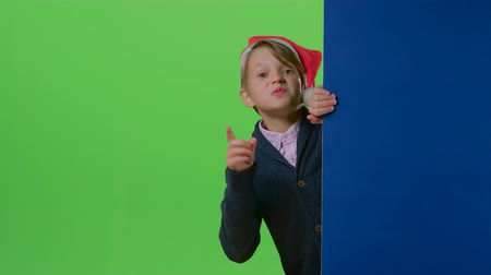 hides : Teenage boy in christmas hat emerges from behind the boards and waving his index finger on a green screen