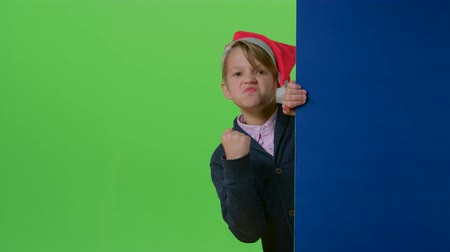 hides : Teenage boy in christmas hat emerges from behind the boards and shows his fist on a green screen