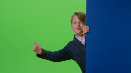 hides : Child boy appears from the side board waving hand and calling to his on a green screen