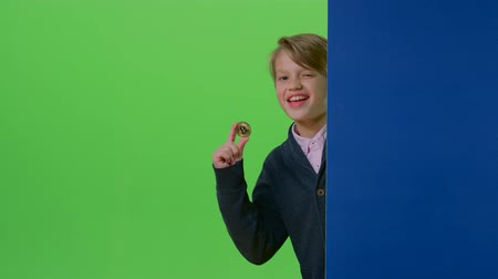 hides : Teenager peeks out from behind a board shows the coin and the trumb up on a green screen Stock Footage