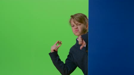 hides : Teenager peeks out from behind a board shows the coin and dislike on a green screen