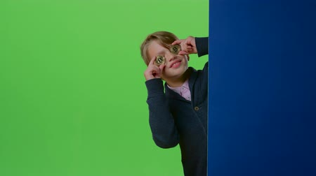hides : Teen comes out from behind the wall with two coins on a green screen Stock Footage