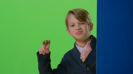 hides : Teenager comes out from behind the wall shows the coin and the trumb up on a green screen