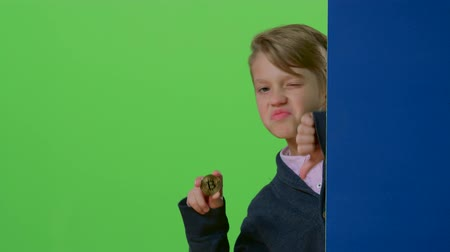 hides : Teenager comes out from behind the wall shows the coin and dislike on a green screen