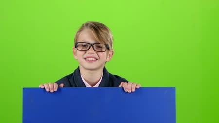 hides : Child boy in the glasses looks out from under the board holding on to her on a green screen. Slow motion