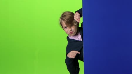 indicação : Child boy peeps out from the side board and nods his head on the green screen. Slow motion Stock Footage