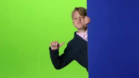 indicação : Teen peeks out from the side the boards and shows dislike on a green screen. Slow motion Stock Footage